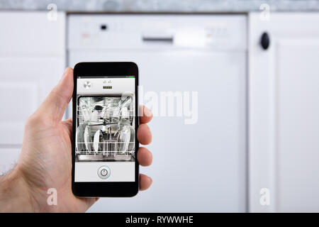 Close-up Of A Person's Hand Operating Dishwasher With Smartphone - Stock Photo