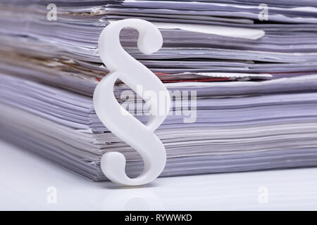 Close-up Of Red Paragraph Symbol Leaning On Documents