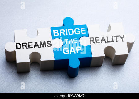 High Angle View Of Text On Puzzle Piece Over Gray Backdrop - Stock Photo