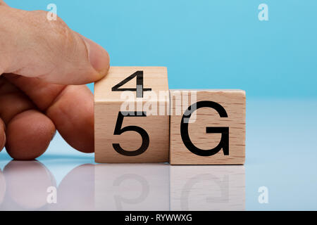 Man's Hand Changing Wooden Block From 4g To 5g On White Surface - Stock Photo
