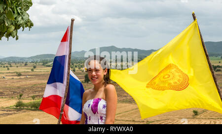 teen standing between  thai and temple flags on windy day with fields and mountains in the back ground