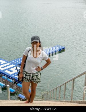 Asian woman with hat standing on top steps with water below... - Stock Photo