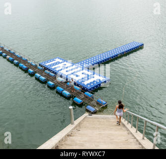 Teenager walking down stairs and mother standing on float at resevoir in Thailand - Stock Photo