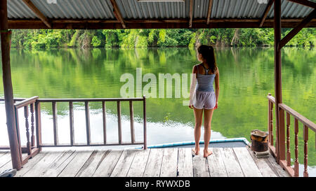 Young Asian girl standing on covered deck looking at river in Thailand - Stock Photo
