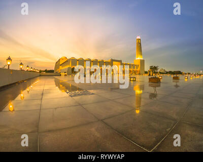 Wide angle view of State Grand Mosque with a minaret at twilight reflecting on marble pavement outdoors. Qatar State Mosque, Middle East, Arabian - Stock Photo