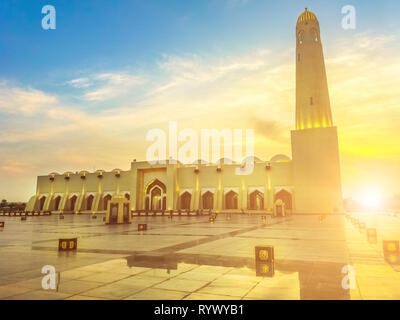 Scenic State Grand Mosque with a minaret at sunset light reflecting on marble pavement outdoors. Doha mosque in Downtown, Qatar, Middle East, Arabian - Stock Photo