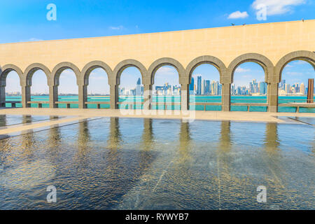 Modern skyscrapers of Doha West Bay skyline through series of arches along a walkway from museum in Qatari capital. Doha in Qatar seafront. Middle - Stock Photo