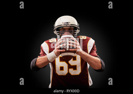 Portrait of American football player holding a ball with both his hands Stock Photo