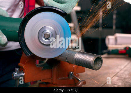 Gloved hands hold an angle grinder and cut the pipe, many sparks fly to the sides - Stock Photo
