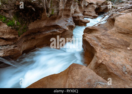 Water flowing and cascading through a sand stone slot canyon. Silky water effect with flowing blue water. - Stock Photo