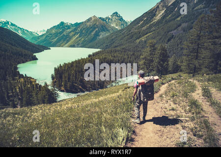 Lake with rocky ridge. Beautiful landscape. The tourist goes over the rocks on the shore of the lake. Altay Russia - Stock Photo