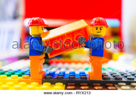 Poznan, Poland - March 14, 2019: Two Lego construction workers carrying together a orange brick. - Stock Photo