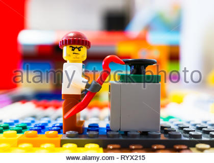 Poznan, Poland - March 14, 2019: Lego thief trying to open a safe with a crowbar. - Stock Photo