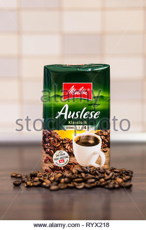 Poznan, Poland - March 12, 2019: German Melitta Auslese classic coffee in a green package and coffee beans on a wooden table in soft focus background. - Stock Photo