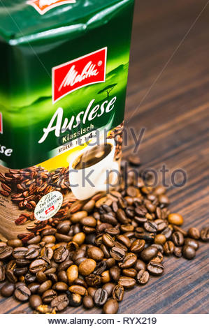 Poznan, Poland - March 12, 2019: Melitta Auslese coffee in a package and fresh roasted beans on a wooden surface in soft focus. - Stock Photo