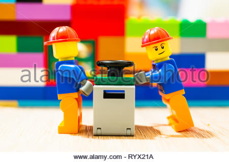 Poznan, Poland - March 14, 2019: Two Lego construction workers pushing together a safe. - Stock Photo