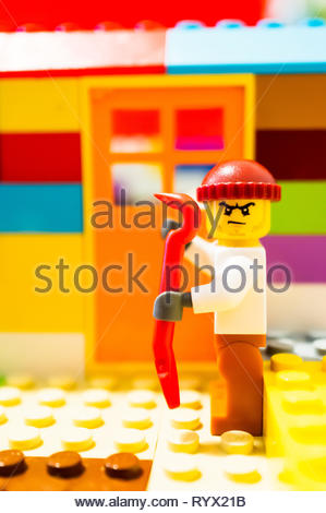 Poznan, Poland - March 14, 2019: Escaped Lego prisoner holding a crowbar planning to break into a house. - Stock Photo