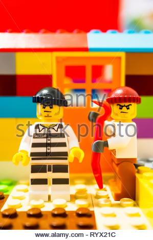 Poznan, Poland - March 14, 2019: Two Lego escaped prisoners trying to break in a house with a crowbar. - Stock Photo