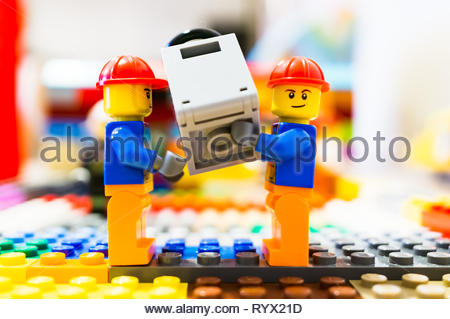 Poznan, Poland - March 14, 2019: Two Lego construction workers carry together a safe. - Stock Photo