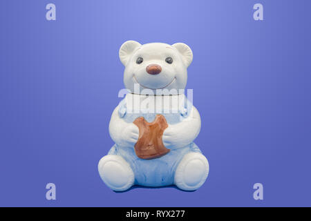 A glazed pottery cookie jar in the shape of a teddy bear  isolated on blue background - Stock Photo