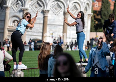 Tourists pose for photographs in front of the leaning tower of Pisa in Tuscany, Italy. - Stock Photo