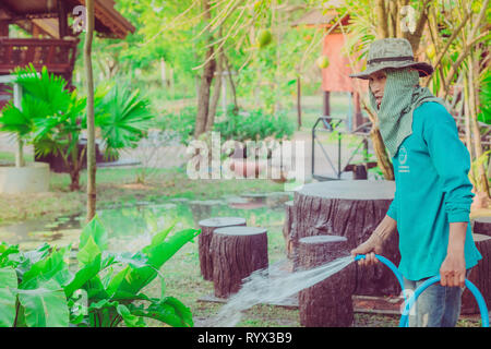 KANCHANABURI-THAILAND, March 2, 2019 : Unidentified Senior man watering plants with hose and working in garden at his home on March 2,2019 in Kanchana - Stock Photo