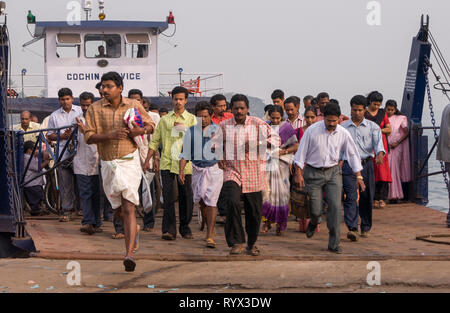 Ferry arriving in Cochin in the early morning with local people rushing off - Stock Photo