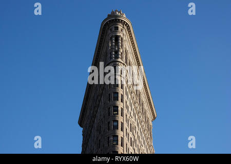 Clean image of the Flatiron Building in New York City with a bright blue sky - Stock Photo