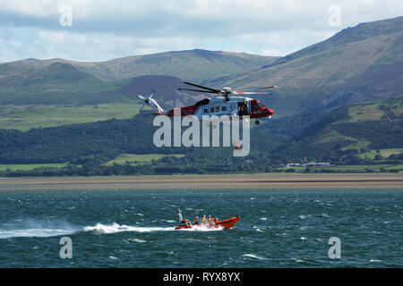 HM Coastguard helicopter and Beaumaris lifeboat practice transferring a rescued person on the Menai Strait with Snowdonia mountains in background - Stock Photo