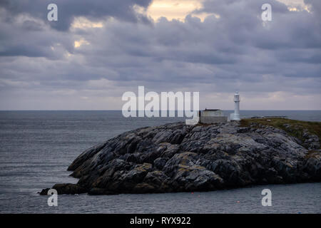 Lighthouse on the rocky Atlantic Ocean Coast during a cloudy sunset. Taken in Channel-Port aux Basques, Newfoundland, Canada. - Stock Photo