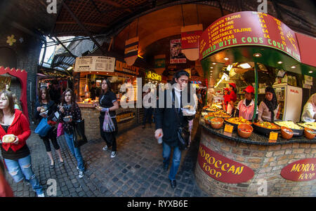 London, United Kingdom - March 31, 2007: Unknown shoppers eating street food while walking at Camden Lock, famous market at UK capital. Extreme wide - Stock Photo