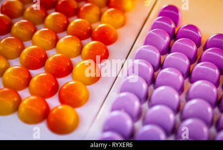 White chocolate shell with passion fruit ganache center and white chocolate truffle filled with creamy cranberry . Chocolate pralines. Bonbons. - Stock Photo