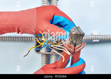 Repairman in protective gloves is cutting the wire ends with nippers tool while installing junction box. - Stock Photo
