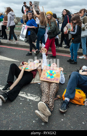 London, UK. 15th March, 2019. School students campaigning against climate change protest outside Parliament. Credit: Maggie sully/Alamy Live News. School children on strike to protest at climate change gathering outside Parliament and on Westminster bridge London.  Some students lay down on Westminster Bridge while others march by with placards. Part of the worldwide 'FridaysforFuture' protest. - Stock Photo