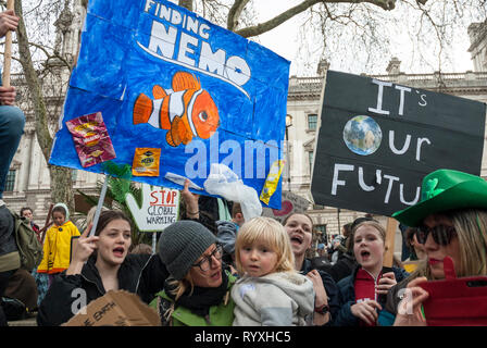 London, UK. 15th March, 2019. School students protesting, part of the 'FridaysforFuture' climate change protest outside Parliament. Credit: Maggie sully/Alamy Live News. School students and young children went on strike to  protest at climate change and gathering outside Parliament, London. Young girls with a colourful banner about 'finding Nemo' among plastic pollution in our seas, and 'Its our future'. - Stock Photo