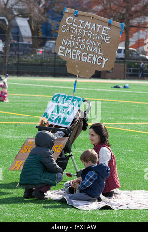 Seattle, Washington: A family attends a rally in Cal Anderson Park in support of the Green New Deal and to draw attention to the lack of action on climate change. The Seattle Youth Climate strike was held in is solidarity with the worldwide Climate Strike movement. Credit: Paul Christian Gordon/Alamy Live News - Stock Photo