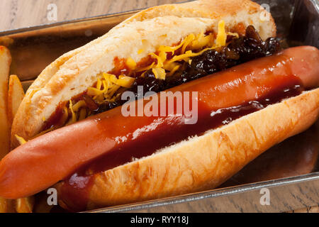 Hot Dog santwich with french fries and salad served in alluminium rectangular dish - Stock Photo