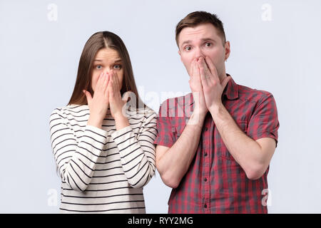 Shocked amazed young couple covering mouth with hands looking at camera - Stock Photo