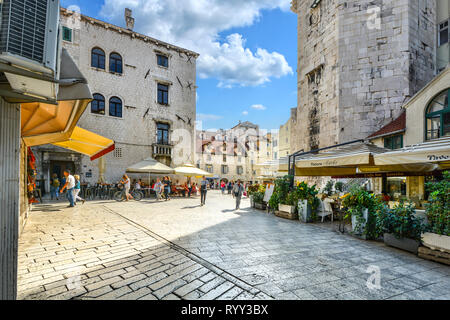 Tourists enjoy a sunny summer day at shops and cafes on the Fruit Square or Voćni trg, in the Diocletian's Palace section of Old Town Split, Croatia - Stock Photo