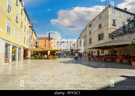 Tourists sightsee and dine at outdoor cafes at People's Square inside Diocletian's Palace in the old town center of Split Croatia. - Stock Photo