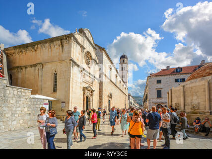 Crowds of tourists walk the main street or stradun next to St Saviour Church in the ancient walled city of Dubrovnik, Croatia. - Stock Photo