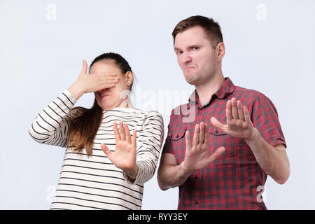 Portrait ofyoung couple looking on something unpleasant gesturing with hands refusing to buy it - Stock Photo