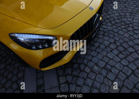 Yellow Mercedes-Benz AMG GT C parked on paving stones - Stock Photo