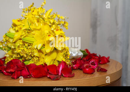 Yellow wedding bouquet over the table with red petals roses - Wedding bouquet - Image - Stock Photo