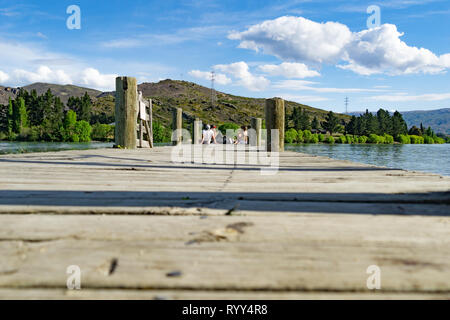 CROMWELL, NEW ZEALAND - OCTOBER 21 2019;  Group four youth sitting socializing  on end of pier on Lake Dunstan - Stock Photo