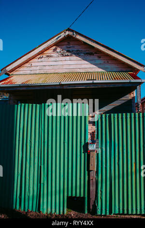 derelict house with green fence - Stock Photo