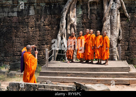 Novice monks posing for a picture at Ta Prohm in Siem Reap, Cambodia - Stock Photo