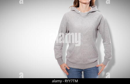 Shirt design and fashion concept - young woman in gray sweatshirt, gray hoodies, blank isolated on grey background. mock up - Stock Photo