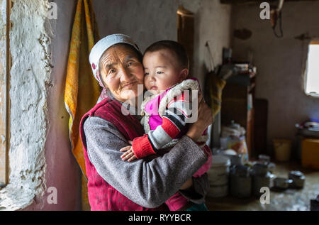 bayan Ulgii, Mongolia, 30th September 2015: mongolian kazakh nomad granmother holding a boy on her lap inside a winter house - Stock Photo