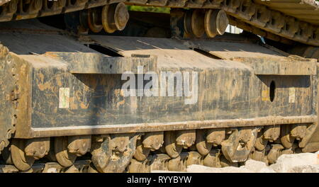 The big tire of an excavator in the factory site it has big chains of tires from the industrial site - Stock Photo